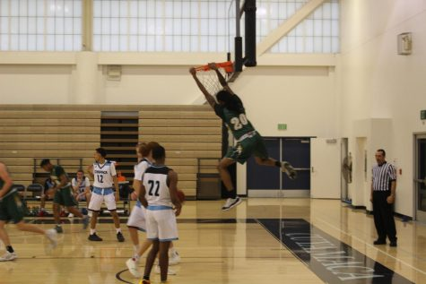 Freshmen Forward Jamal Johnson hangs from the rim after dishing a fierce dunk on the Coyotes.